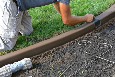 Trowelling for smoothness in a freshly created concrete edging around a flower bed