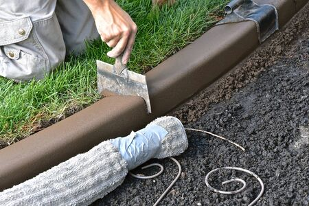 Cutting expansion joints  in a freshly created concrete edging around a flower bed