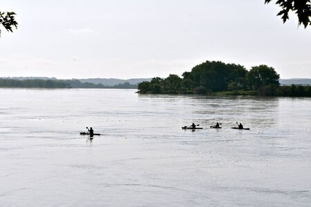 A group of kayakers are silhouetted as they paddle across a river. Stockfoto