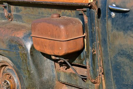An old rusty gas tank is attached to the frame of a aged pickup Stock Photo
