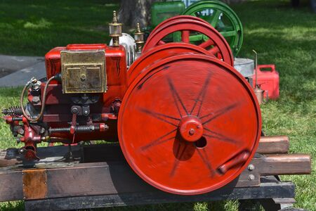 A red refurbished antique portable gas engine in operation with a huge  spinning flywheel. Stock Photo