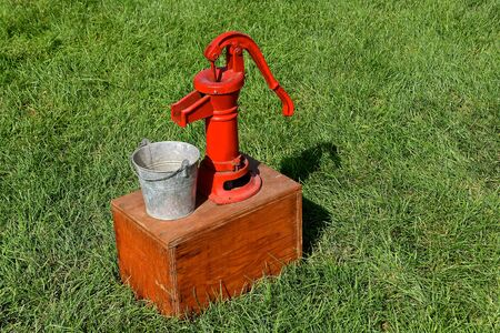 An old red hand pump and pail is displayed on top of a wooden box.