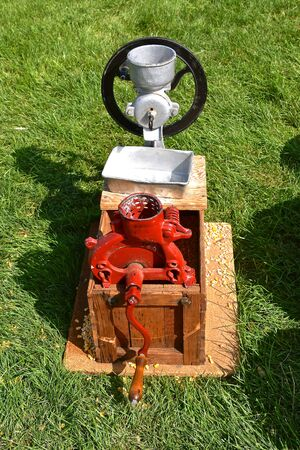 An old red hand powered corn sheller removers the kernels of corn which is powered by hand cranking.