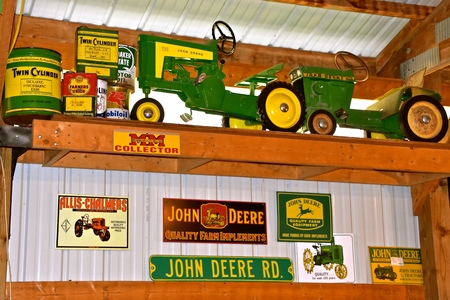 ALEXANDRIA, MINNESOTA, July 28, 2019: The vintage John Deere advertising toys, objects, and signs products of John Deere Co, an American corporation that manufactures agricultural and construction equipment, drive trains, and transmission.
