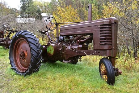 VERGAS, MINNESOTA, October 4, 2019: The old John Deere tractor with a missing front wheel is a  products of John Deere Co, an American corporation that manufactures agricultural and construction equipment, drive trains, and transmission.