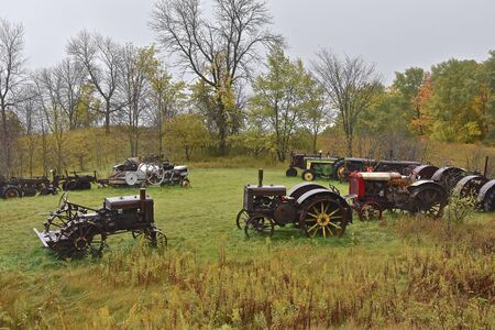 VERGAS, MINNESOTA, October 4, 2019: The old John Deere tractors parked on a hill  products of John Deere Co, an American corporation that manufactures agricultural and construction equipment, drive trains, and transmission.