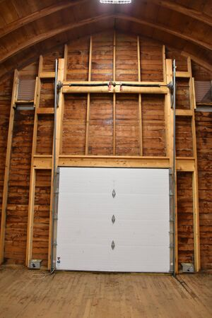 Modernized hayloft of a barn where the end has double doors with an outdoor stairway.