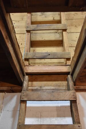 A wooden wall ladder used to climb to a hayloft of a barn continues to curve with the roof  allowing easy debarking unto the the next level. Stockfoto