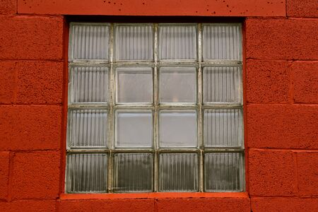 Sixteen square  glass window  blocks create a huge barn window surrounded by red painted block