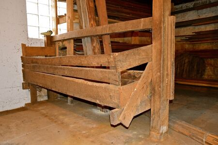 An old hay manger made from rough wood in a barn has been cleaned
