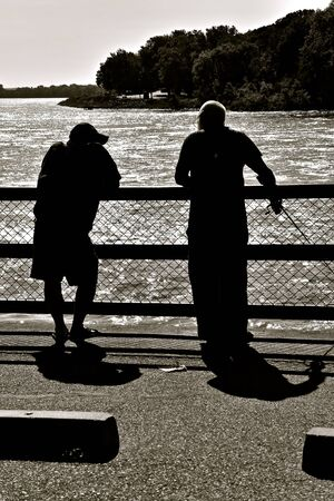 Silhouetted are several old buddies leaning against railings as they fish and converse