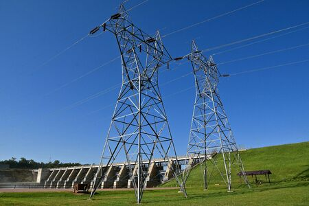 Huge electrical transmission towers are located in front of a dam with multiple spillways.