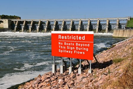 Posted is a sign restricting boats from coming to close to the spillways of a dam Фото со стока