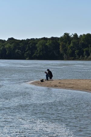 A lone unidentified fisherman on a sand bar fishes along a river.