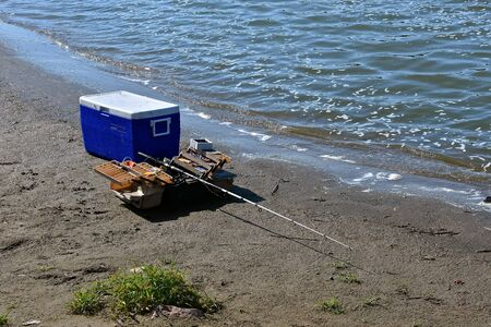 A fisherman leaves a cooler, rod and reel, and tackle box along the shore of a lake or river.