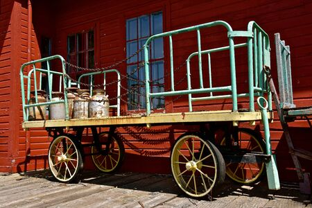 Old metal milk cans are loaded on an wooden cart with metal sides.