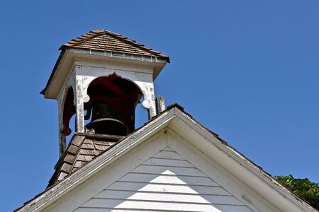 An old schoolhouse belfry with a bell inside partially hidden by shadows