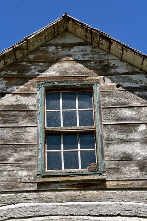 A robins nest is built on the ledge of a window of a two tory old log cabin. Stockfoto