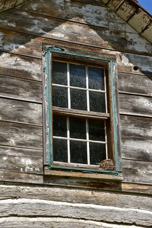 A robin nest is built the  window ledge of an old log cabin