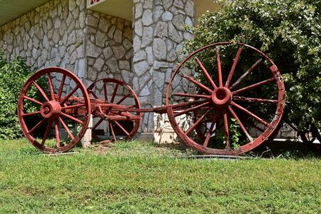 The hub and spokes of an old wooden wagon or cart wheel pulled by a team of horses shows signs of wear and deterioration. Stockfoto