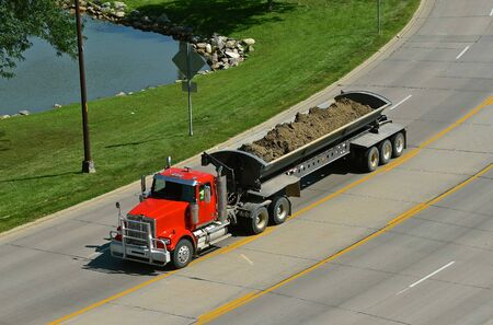 A loaded truck carrying  a heavy load of landfill from a construction site travels down a highway.