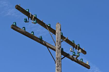 Old telephone pole with green glass insulators against bright blue sky