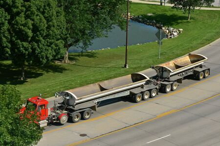 An unloaded truck  with double trailers used for carrying landfill or debris from a construction site travels down a highway.