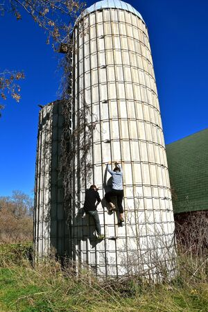 Two unidentified people climb the outside rings of a rib stone concrete silo.