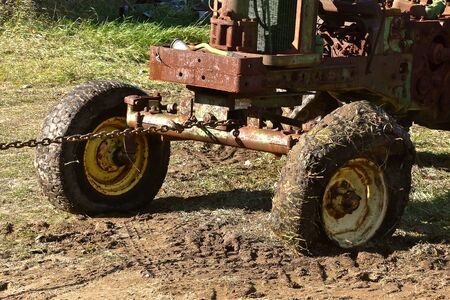 An old wide front junked tractor is being towed with a chain in the mud