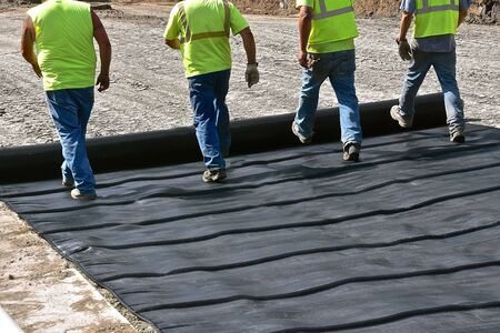 Vested construction workers unroll a layer of tarpaulin  in a road construction project