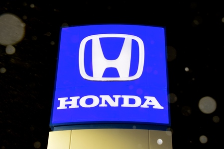 BEMIDJI, MINNESOTA, October 12, 2019: Snowflakes are falling on the Honda  logo sign, which Honda logo on a panel. Japanese public multinational corporation primarily known as a manufacturer of automobiles, motorcycles and power.equipment.