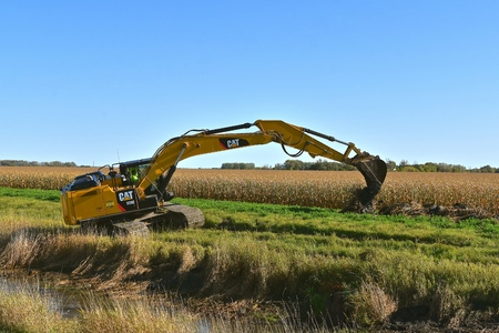 SABIN, MINNESOTA, October 6, 2019: Founded in 1925, the 329E Cat excavator moving a scoop of earth from a ditch  is from Caterpillar Inc., an American corporation which designs, develops, engineers, manufactures, markets and sells machinery, and engines Редакционное