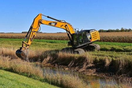 SABIN, MINNESOTA, October 6, 2019: Founded in 1925, the 329E Cat excavator moving a scoop of earth from a ditch  is from Caterpillar Inc., an American corporation which designs, develops, engineers, manufactures, markets and sells machinery, and engines. Редакционное