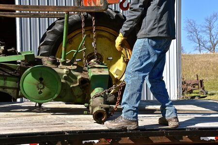 A partial frame of an old tractor, a rear axle and a lone wheel are  being loaded on a trailer