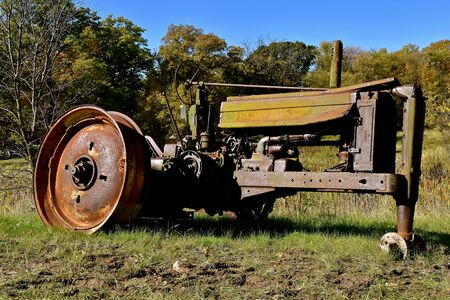 VERGAS, MINNESOTA, October 6, 2019: The old John Deere tractor missing  tires is a  product of John Deere Co, an American corporation that manufactures agricultural and construction equipment, drive trains, and transmission.