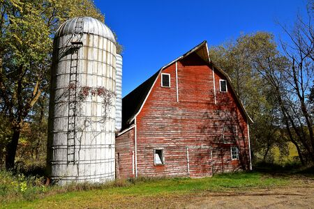 An old red hip roofed barn stands adjacent to a stave silo with a metal roof.