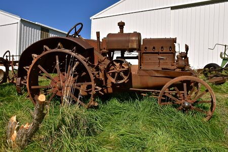 The unidentifiable rusty old tractor on steel wheels is missing  many parts 版權商用圖片