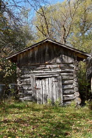 A very old weathered log cabin used many years ago  as a storage shed