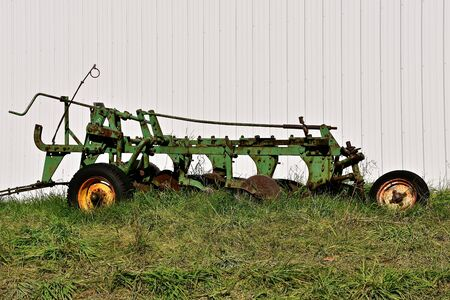 An old green five bottom plow is parked against a metal machine shed.