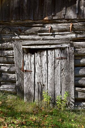 A rickety old door to a weathered log cabin used as a storage shed