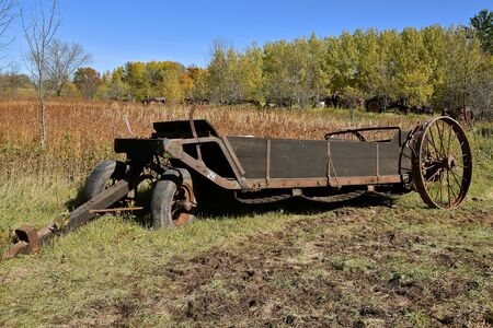 An old pull rusty manure spreader parked in a pasture of long grass in autumn colors