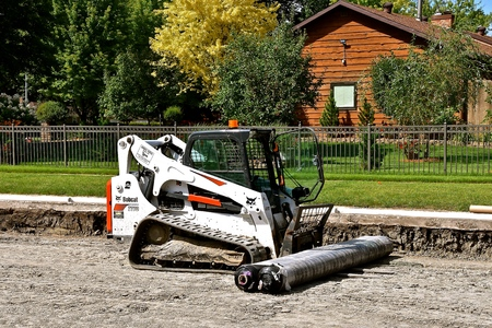 MOORHEAD, MINNESOTA, August 20, 2019: The Bobcat 1770 skid steer moving material on a street condition project in a neighborhood is headquartered in West Fargo, North Dakota.