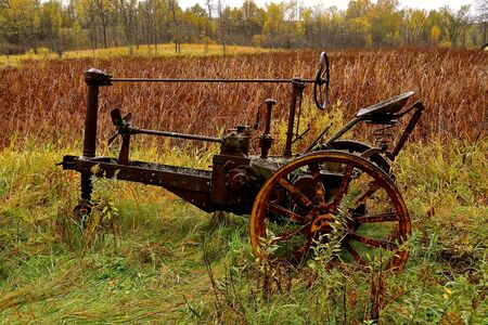 The skeleton frame of an old tractor is surrounded by the colors of autumn