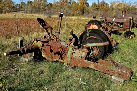 Frame of a very old tractor is left laying in the grass.