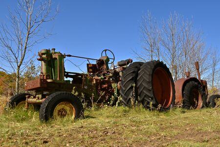 A huge old tractor with a missing engine is left in a salvage and junkyard.