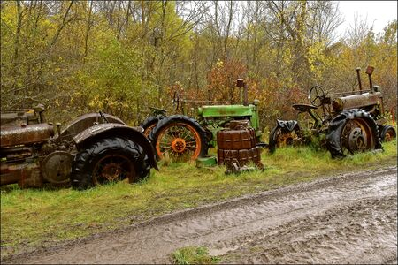 Old discarded tractors are lined up between a woods and a very muddy road