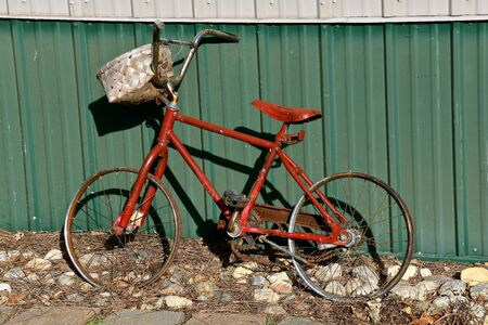 An old bike without tires leans against a metal shed.
