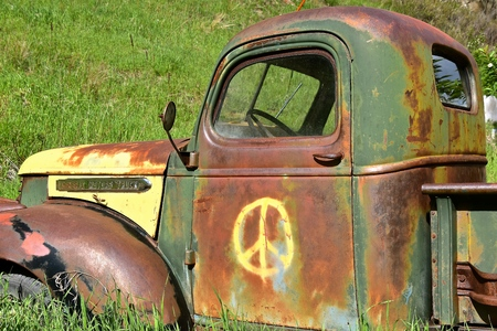 ROCHFORD, SPOUTH DAKOTA, June 24, 2019:  The old rusty truck with a peace sign is a GMC, General Motors Company, is an American automobile division of the American manufacturer