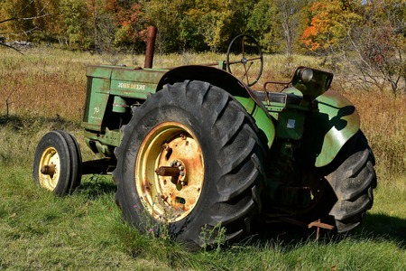VERGAS, MINNESOTA, October 6, 2019: The old John Deere 70 tractor is a  product of John Deere Co, an American corporation that manufactures agricultural and construction equipment, drive trains, and transmission.