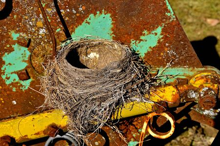 The remains of a robin bird nest is left on the frame of a machine on a farm.